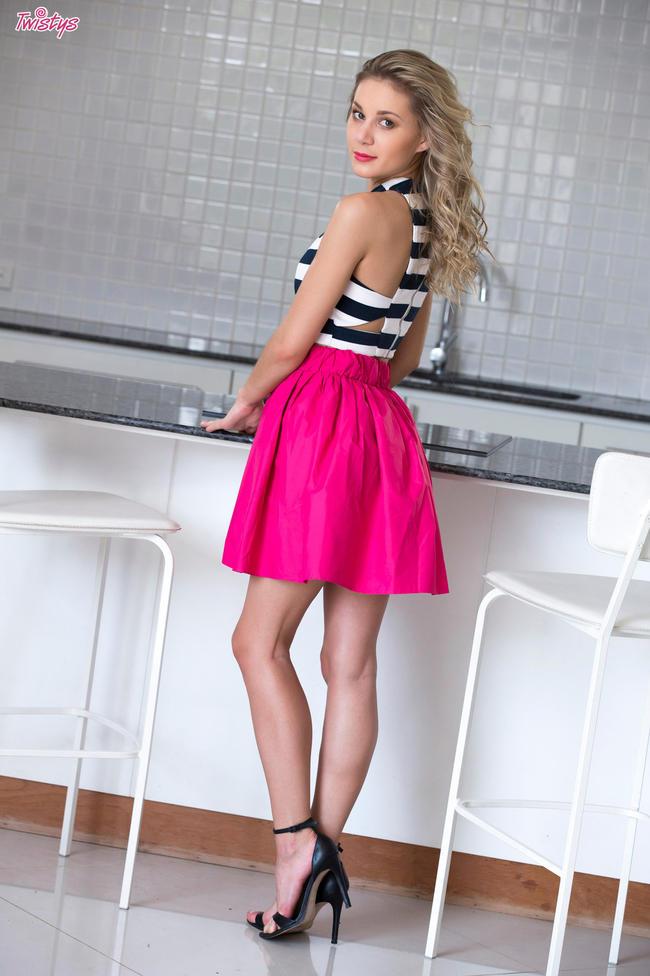 Шаловливая малышка в розовой юбке развлекается на столе
