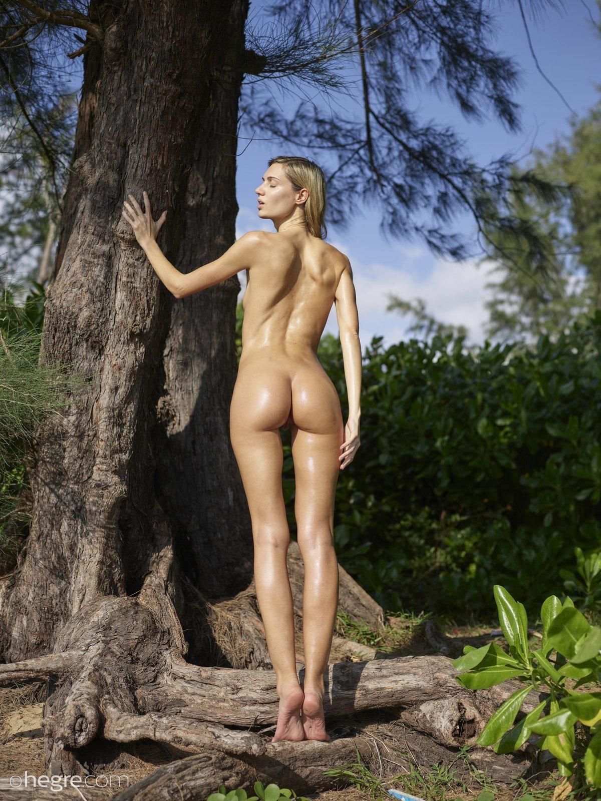 Горячая блондинка позирует обнаженной в лесу