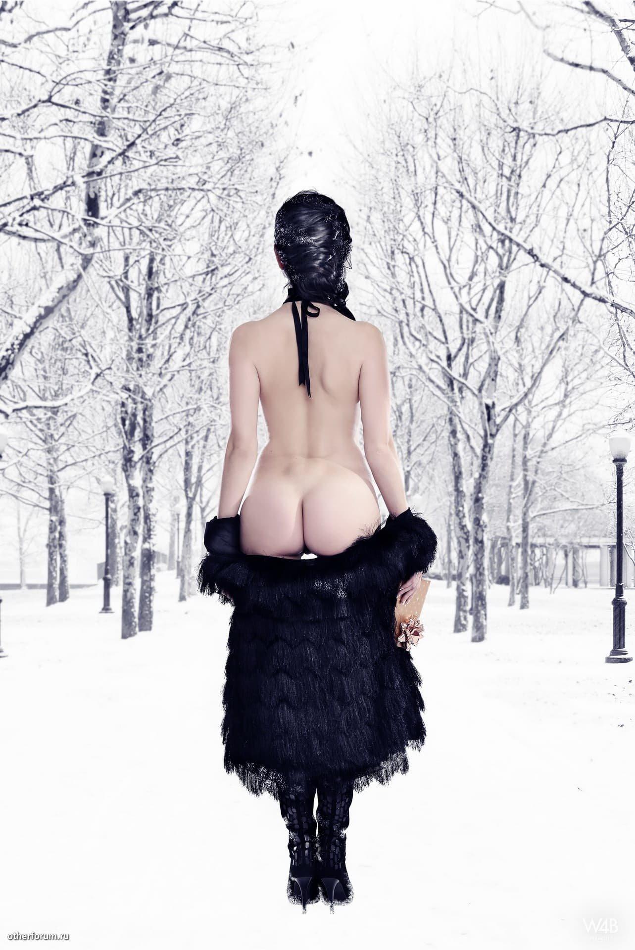Красивая девушка в шубе позирует в лесу зимой