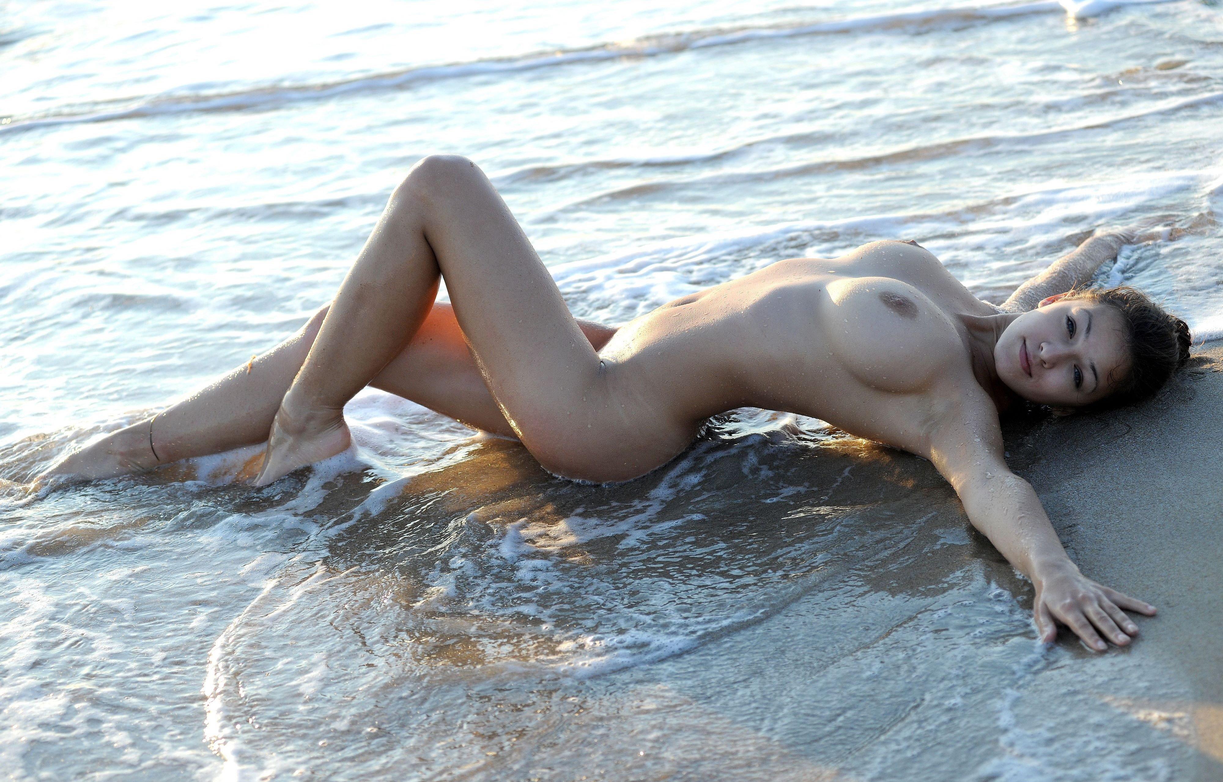 Гибкая девушка раздвигает ноги на пляже