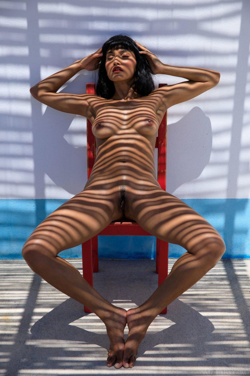 Мулатка с красными губами обнажилась на стуле