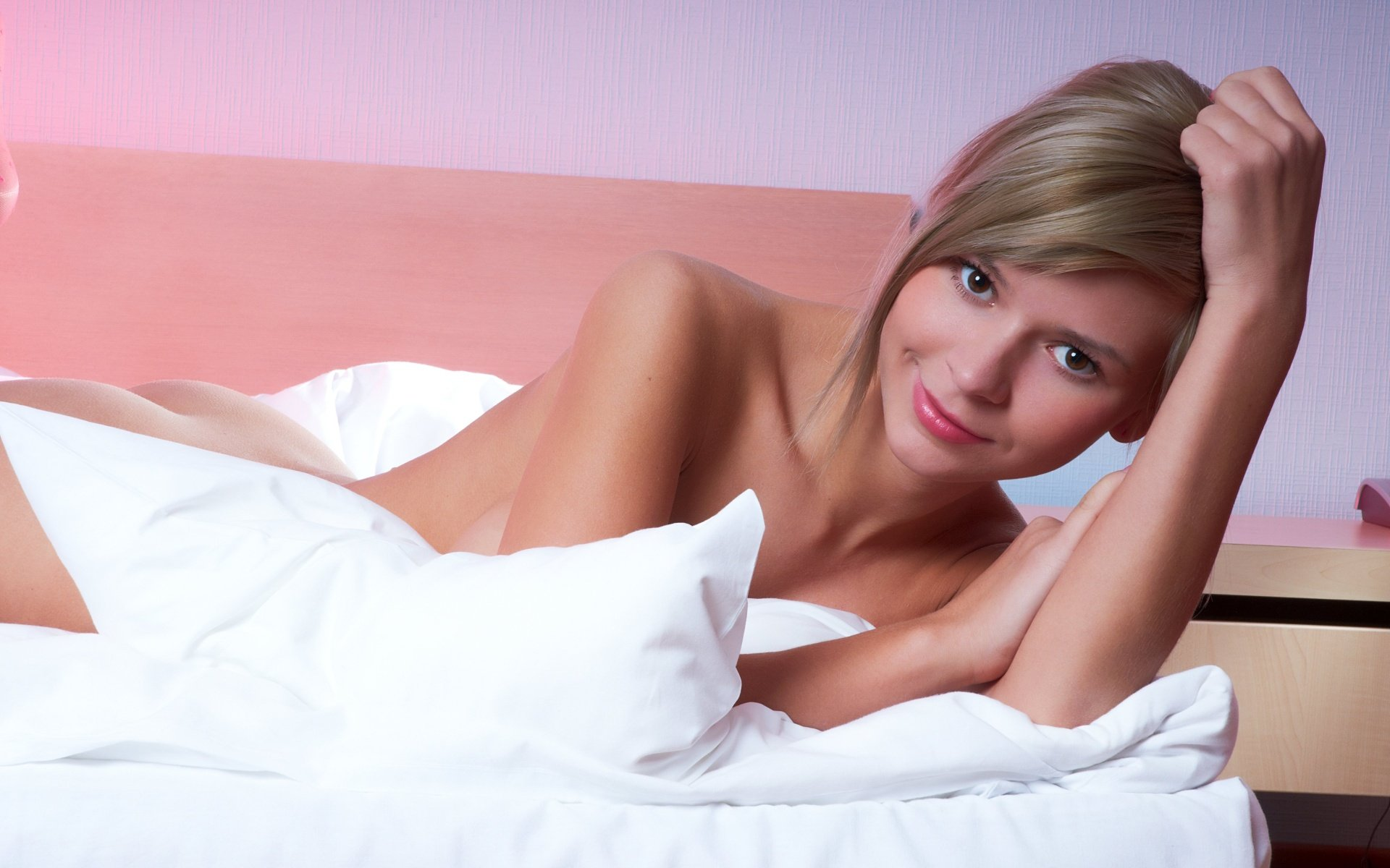 Гламурная детка в розовых чулках на кровати